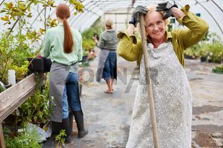 Ältere Gärtnerin und Kollegen arbeiten zusammen