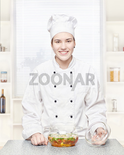 Chef with a soup in a glass pot