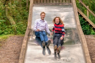 Young couple having a lot of fun on a big metal slide in the woods. Looking at camera