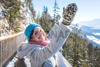 Happy young woman is raising her hands on the mountain, enjoying the view over Salzburg. Winter time on Gaisberg, Salzburg, Austria