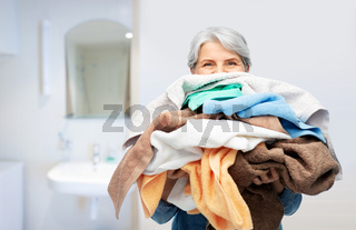 senior woman with heap of bath towels