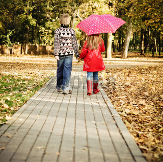 Little boy and little girl in the autumn park