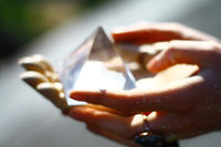Hands holding glas pyramid, brightly illuminated