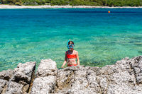 Little girl in a snorkeling mask coming out of the sea onto the rocky shore