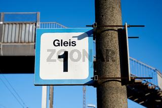 Schild mit der Aufschrift Gleis 1 an einem kleinen Bahnhof