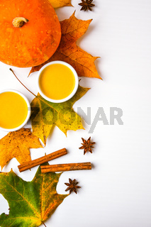 Autumn food. Pumpkin puree soup, leaves. Top view. Autumn harvest, pumpkins, leaves on grey as abstract background. Thanksgiving day. Flat lay.