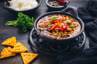 Bowl of chili con carne with rice and toppings on wooden table
