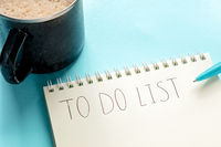 To do list, handwritten in a notepad, with a cup of coffee and a blue pen