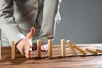 Business woman hand stop domino effect