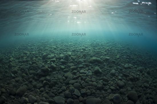 Sonnenstrahlen fallen auf Steine im Uferbereich