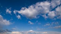 White cumulus clouds and rainbow in summer evening blue sky background