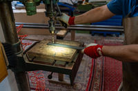 A metal worker drilling holes in metal with a bench drill