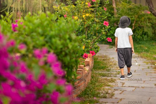 Boy walking in a tropical garden
