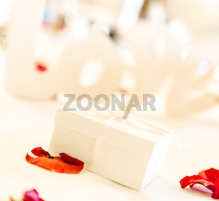 White gift box and red rose petals