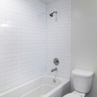 Square frame Interior of a bathroom with vanity sink and shower tub combo with subway tiles wall surround