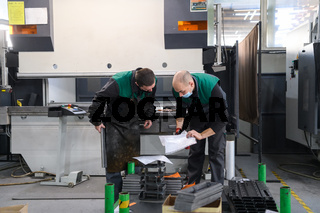 two workers wearing a protective mask due to a coronavirus pandemic, working in a modern factory and preparing a program and material for a cnc machine