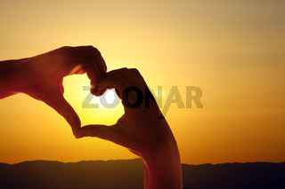 Hand shaped heart against sunset. Valentines day concept