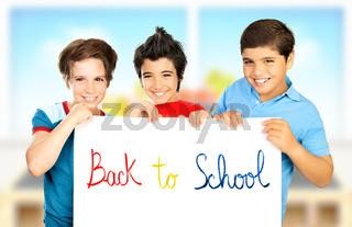 Three classmate boys playing in classroom
