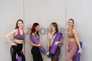 Athletic girls in sports out fits standing next to the wall holding a yoga mat, smiling on camera. Practicing in fitness or yoga studio, working out indoor. Isolated on grey background
