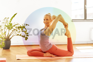 woman doing mermaid pose at yoga studio