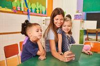 Erzieherin und Kinder machen Selfie mit Tablet Computer