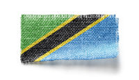 Tanzania flag on a piece of cloth on a white background