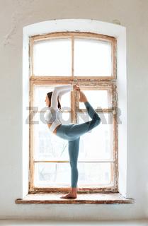 Woman doing yoga near shabby window