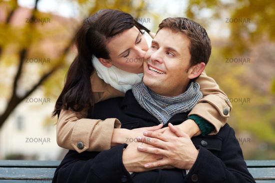 Frau küsst Mann im Park