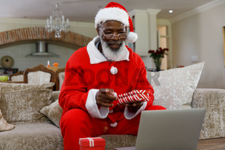 Senior african american man wearing a costume of santa claus and holding gifts