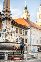 Traveler exploring old town on environmentally friendly electric scooter. Female tourist exploring Ljubljana's old medieval historical city center, taking picture of a fountain with her phone.