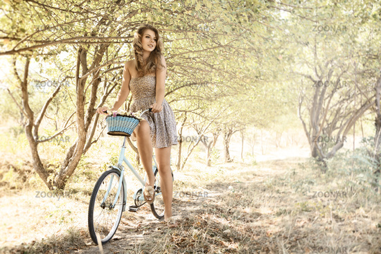 Young woman with bicycle in a park