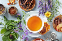 Tea. Herbs, flowers and fruit around a cup of tea, an overhead flat lay shot
