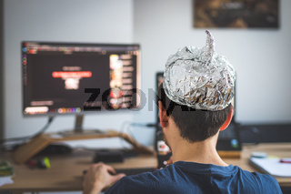 Conspiracy theory concept: young man is wearing aluminum head, sitting in front of the pc watching videos