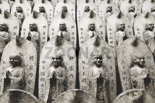Stone buddhist statues in a line at the Daisho-in temple at Miyajima, Hiroshima, Japan