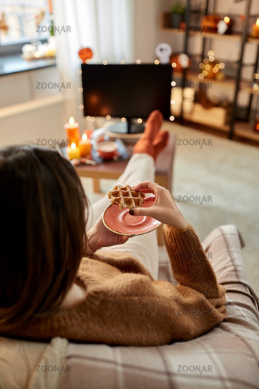 woman watching tv and eating waffle on halloween