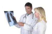Arzt und Patientin sprechen über Röntgenbild einer Lunge