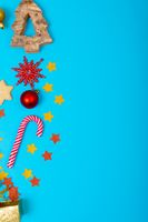 Composition of christmas decorations with candy canes and copy space on blue background