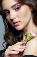 Beauty portrait of young woman Pink carnation flower in hand.