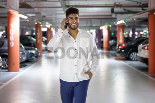 Confident, young handsome man walking along the parking lot while talking on the phone after having parked his car.