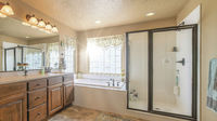 Pano Home bathroom interior with bathtub shower stall and double sink vanity unit