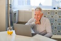 Senior am Laptop Computer freut sich über Videoanruf