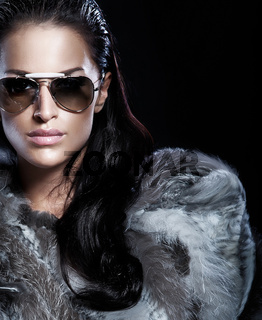 Portrait of brunette woman wearing sunglasses and beautiful fur