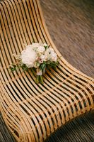 bridal bouquet of white peonies, roses, pink eustoma, astilbe and branches of eucalypt tree on a straw chair