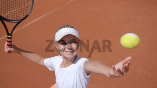 A young tennis player serves in the game.