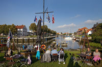 People in the beer garden of the Alte Werft in front of the historic harbor, Toenning, Germany