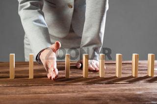 Business woman interrupting domino effect