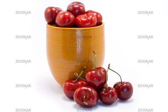 Juicy ruby red cherries in an orange cup