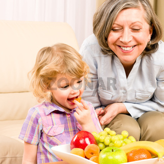 Little girl eat apricot fruit with grandmother