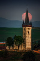 colorful red moon at sunrise in the background, church in the foreground