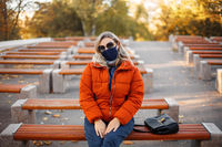 Woman in mask and outerwear in park